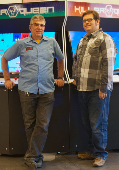 Killer Queen creators Nikita Mikros and Joshua DeBonis stand with their 10-player arcade cabinets. (Photo: Polygon)